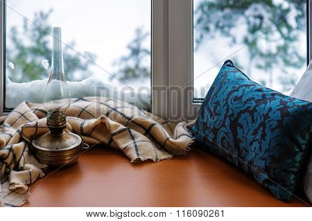 .beige Woolen Scarf And Old Lamp Located On Stylized Wooden Window Sill.