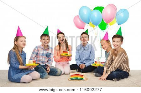 happy children in party hats with birthday cake