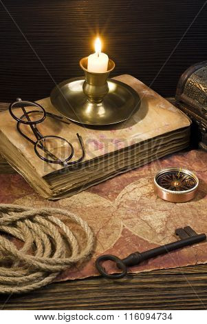 ancient books with candle and Compass on the old paper background