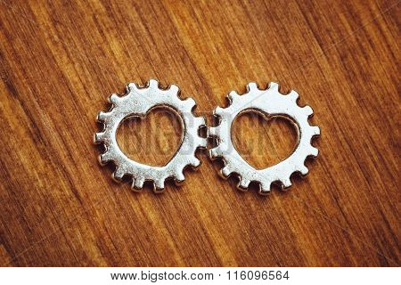 gear wheels with heart symbol, wooden background