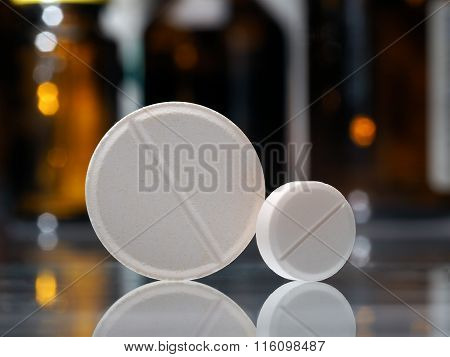 Two tablets. White pills, big and small. Background - dark bottles with medicine