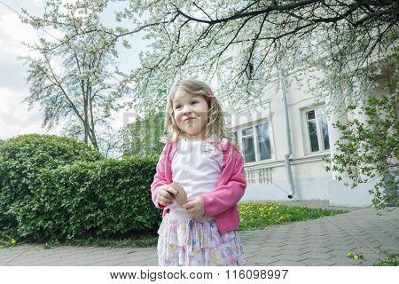 Outdoor funny portrait of grimacing girl in blooming fruit tree garden with pocket mirror in hand