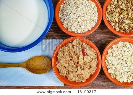 Four small bowls with different cereals and bowl with milk, healthy food