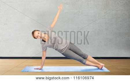 woman making yoga in side plank pose on mat