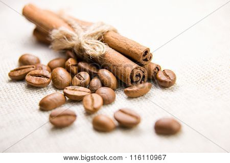 Many Of Roasted Coffee Beans And Cinnamon On The Tablecloth