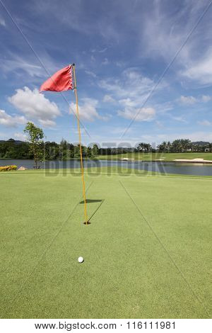 View of golf ball on green with red flag