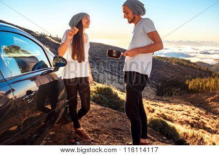 Couple eating having picnic near the car