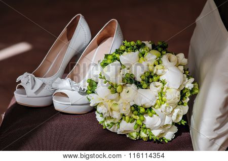 White Bridal Bouquet And White Shoes On The Brown Chair