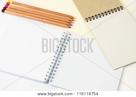 Two Notepad With Different Type Of Paper And Colored Pencils. Five Color Pencils On Table With Notep