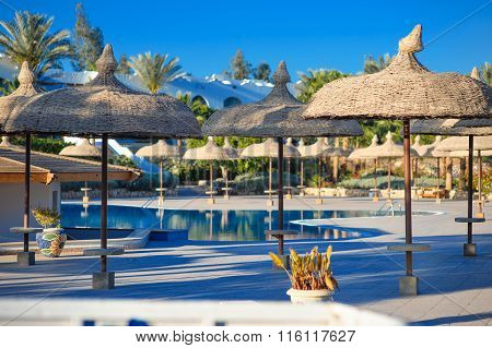 View Of The Pool With Palm Trees And Thatched Umbrellas