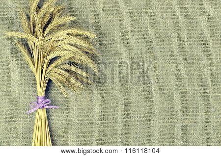 Sheaf Of Wheat Ears On Linen Canvas  Background. Harvest Concept