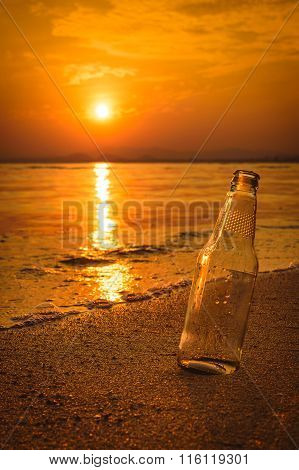Glass Bottle On The Sand At Sunset.