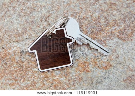 Close Up Of House Shaped Keychain And Key
