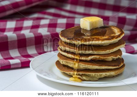 Stack of homemade pancakes with butter and honey on white plate with checkered napkin.
