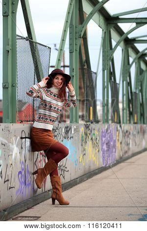 Girl with beautiful legs leaning on a handrail with graffiti
