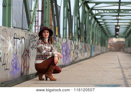 Kneeling girl with hat, pullover and mini skirt