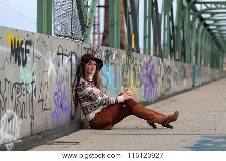 Sitting girl with hat, pullover and mini skirt
