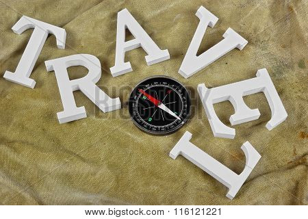 White Sign Travel And Magnetic Compass On Weathered Backpack Background