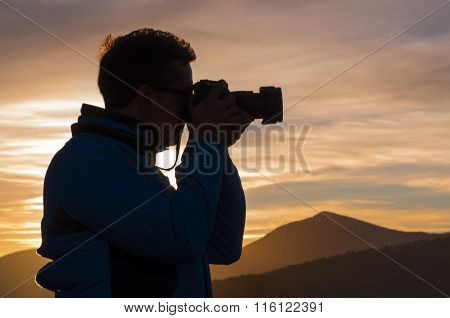 Silhouette Of Photographer Taking Pictures At Sunset