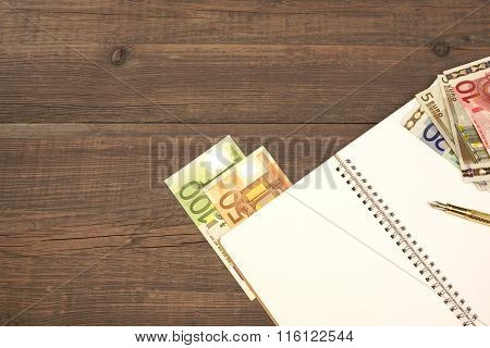 Opened Spiral Notepad  And Euro Cash, Pen On Wood
