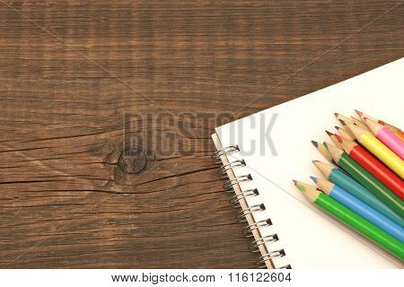 Opened Spiral Notepad With Blank Page And Many Color Pencils