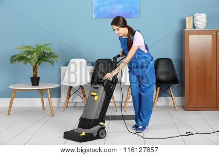 A pretty young woman in uniform vacuuming the floor at the office