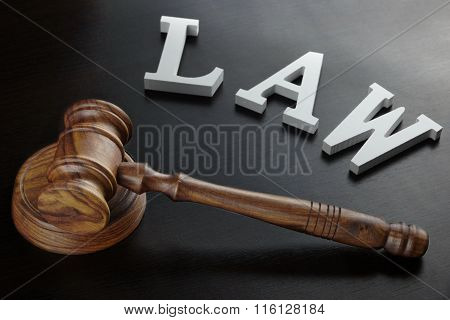 White Sign Law And Judges Gavel On Black Background