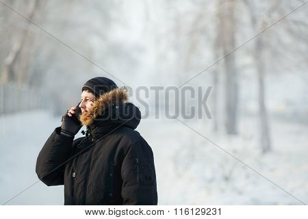 Siberian Man Talking On The Phone Outdoors By Cold Day In A Warm Winter Down Jacket With Fur Hood. S