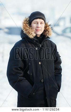 Portrait Of A Young Siberian Man In Cold Winter Day, Wearing Warm Down Jacket With Fur Hood