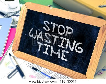 Stop Wasting Time - Chalkboard with Hand Drawn Text.