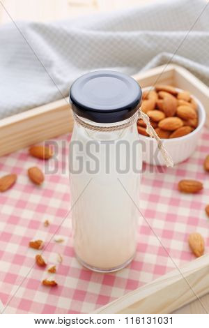 Almond Milk In Bottle With Almonds On Wood Tray
