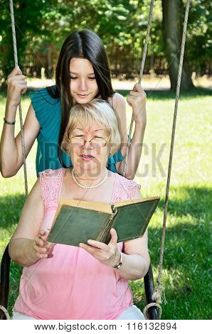 Teen Girl And Her Grandmother Read A Book In The Park Vertical