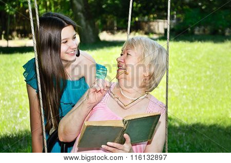 Laughing Cheerful Teen Girl And Her Grandmother Read A Book In The Park