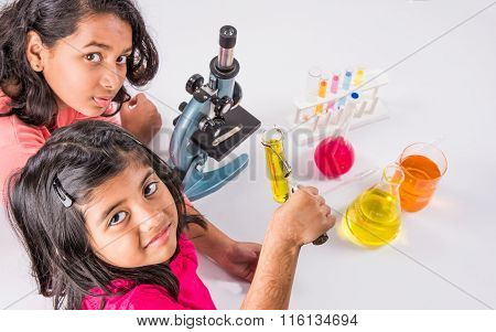 two curious indian girls with microscope, 2 asian girls with microscope, Cute little girls holding m