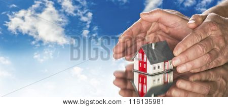 Hands Laying Protectively Around A House