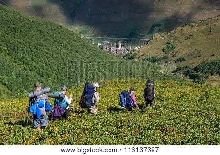 Group of tourists with large backpacks are on mountain