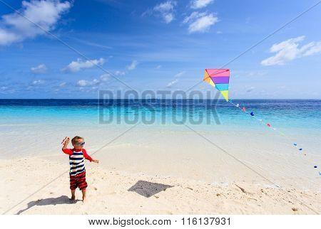 Little boy flying a kite on tropical beach