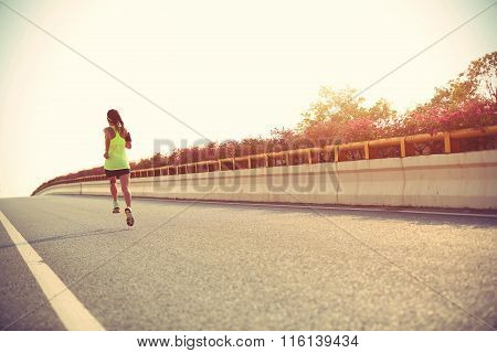young woman runner  running on city road
