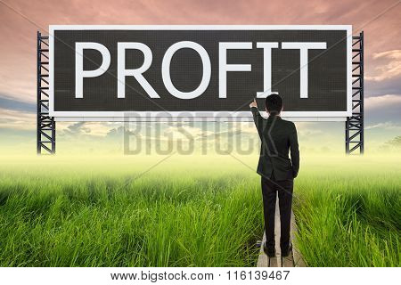 Business Man Standing On Wood Bridge Between Rice Field And Pointing With Large Sign Of Profit