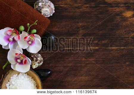 spa concept - towel, salt and orchid on wooden background