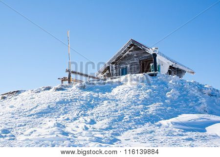 Vacation rural winter background. Small wooden alpine house covered with snow