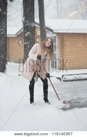 Woman Sweeping The Snowy Street