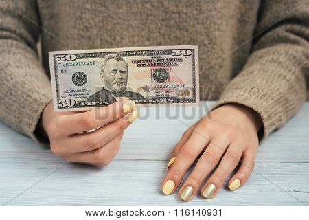 Woman In Brown Sweater With Yellow Manicure Holding A Banknote Of Fifty Dollars, Close-up
