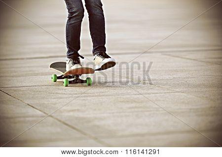 closuep of one skateboarder legs skateboarding on city