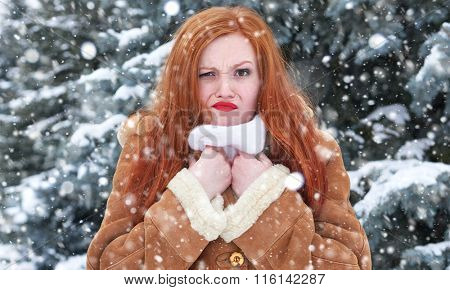 Grimacing woman having discomfort on winter weather, outdoor portrait