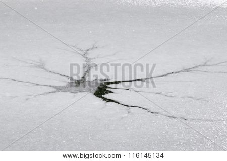 Frozen river water with crack in an ice floe showing surface of water during the snowfall