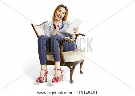 Sitting On Armchair With Tablet