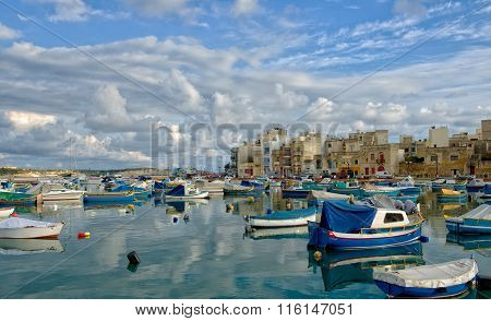 Birzebugga, MALTA-Aug 29: traditional Maltese fishing boats with reflection in maltese village Birze