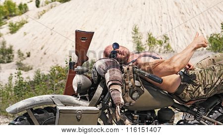 Powerful Bald Biker Is Laying On The Bike On The Desert Background.