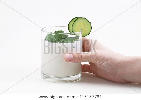 The Female Hand Holds A Glass With Yoghurt